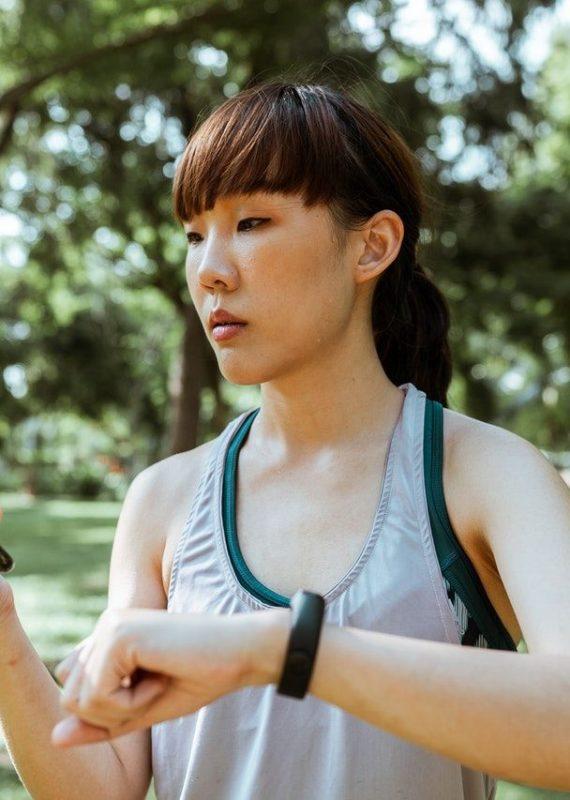 z jakim tętnem biegać - kobieta z zegarkiem do pomiaru tętna