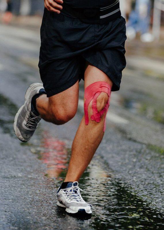 Kinesiotaping w sporcie - biegacz z różowymi plastrami na kolanie