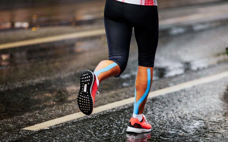 kinesiotaping w sporcie - biegacz z taśmą kinezjologiczną na łydkach
