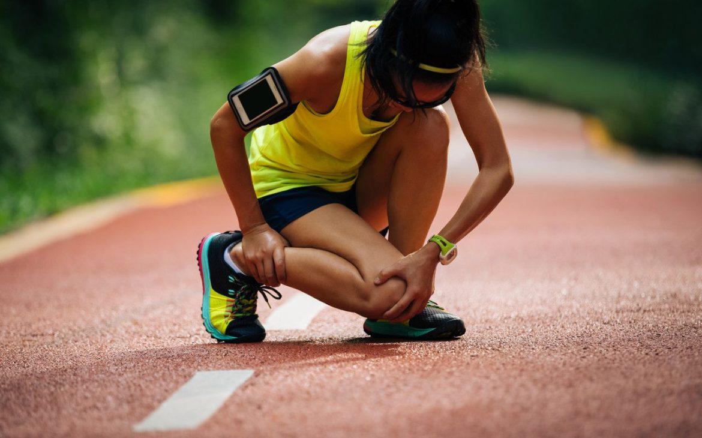 kolano biegacza ćwiczenia - kobieta z bólem kolana podczas biegu