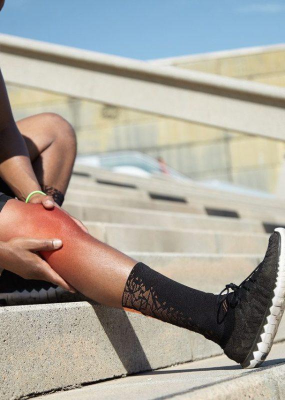 kolano biegacza objawy - sportowiec podczas treningu z bólem kolana