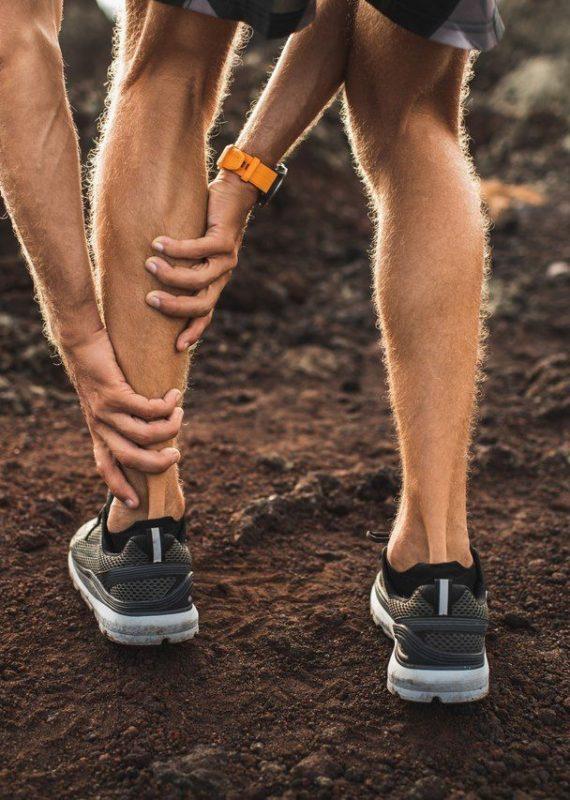 Skurcze łydek podczas biegania - biegacz podczas treningu z bólem łydki